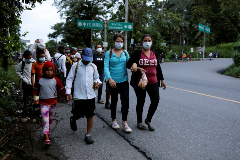 Honduran migrants trying to reach the US walk along a road as they move towards the Mexico border, in Izabal, Guatemala [Luis Echeverria/Reuters]