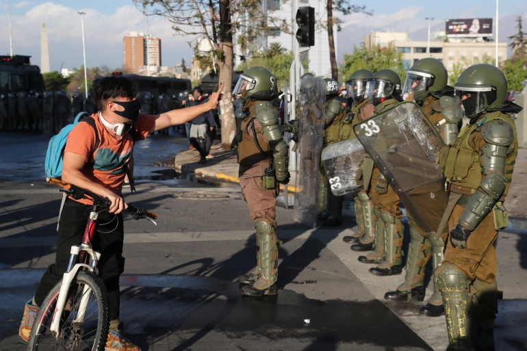 A man confronts riot police during a protest against Chile's government, in Santiago on Friday [Ivan Alvarado/Reuters]
