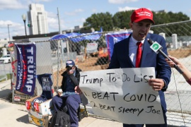 A Trump supporter holds a sign while talking to the media outside the Walter Reed National Military Medical Center, where Trump was being treated for COVID-19 in Bethesda, Maryland [Leah Millis/Reuters]