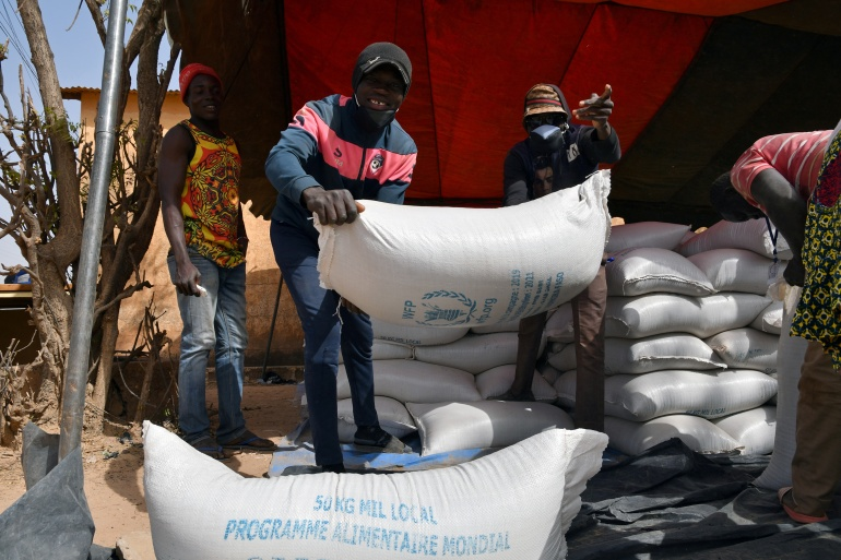 Workers carry aid provided by the World Food Programme (WFP) for distribution in Pissila, Burkina Faso January 24, 2020 [Anne Mimault/Reuters]