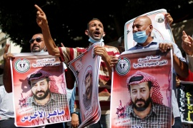 Demonstrators hold pictures of hunger-striking Palestinian prisoner Maher al-Akhras during a rally to show solidarity in Gaza City [Mohammed Salem/Reuters]