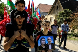 Sevil Aliyeva, 16, carries the portraits of her parents Anar Aliyev and Nurchin Aliyeva who were killed in the Ganja attack as her brother Huseyin Aliyev, 8, cries on the shoulders of a relative during their funeral ceremony in the city of Shamkir, Azerbaijan [Umit Bektas/Reuters]