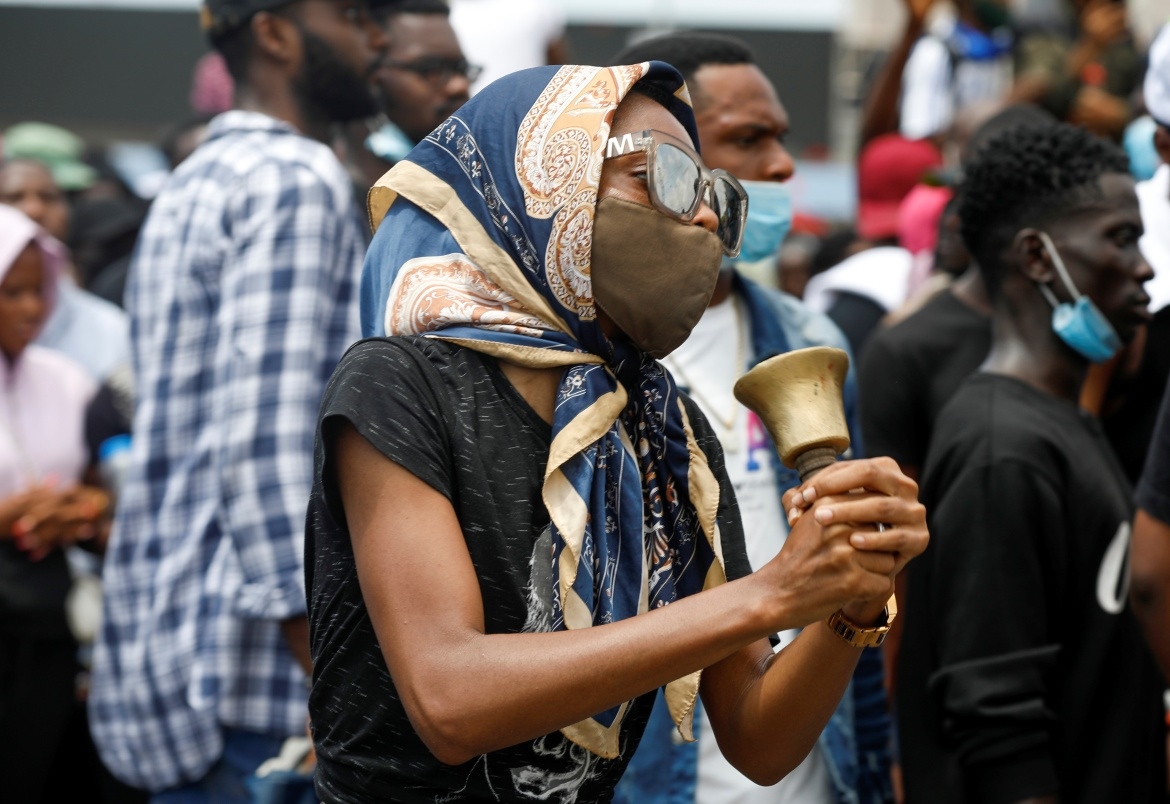 A demonstrator in Lagos carries a bell during a protest in Lagos. Activists and protesters say the announcement did not go for enough and pledged to keep up their pressure campaign. [Temilade Adelaja/Reuters]