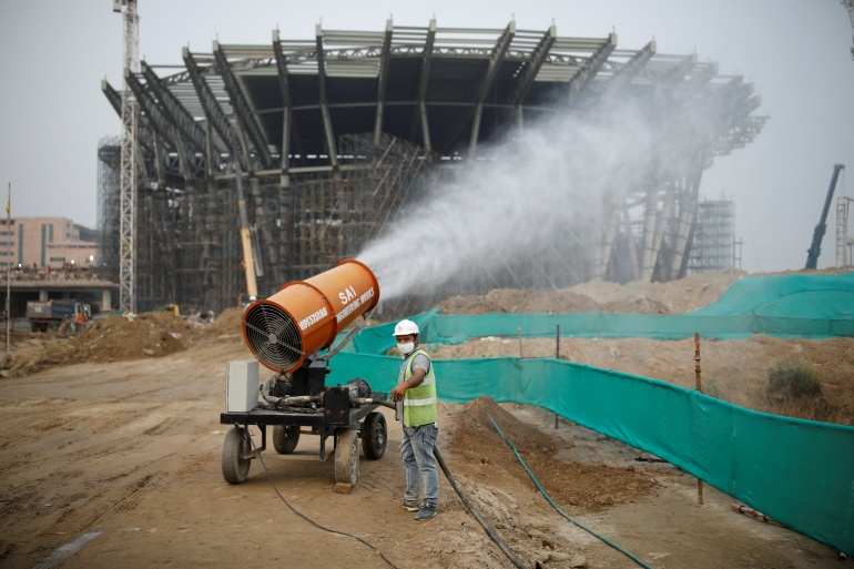 A worker operates an anti-smog gun at a construction site in New Delhi [Adnan Abidi/Reuters]