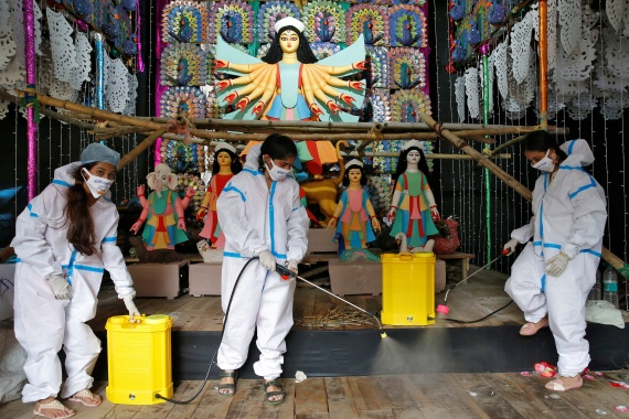 Women wearing personal protective equipment (PPE) sanitise a 'pandal', or a temporary pavilion, ahead of Durga Puja festival in Kolkata [Rupak De Chowdhuri/Reuters]