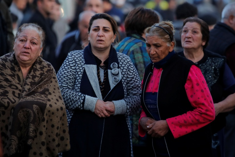 Residents wait at a blast site hit by a missile in Ganja [Umit Bektas/Reuters]