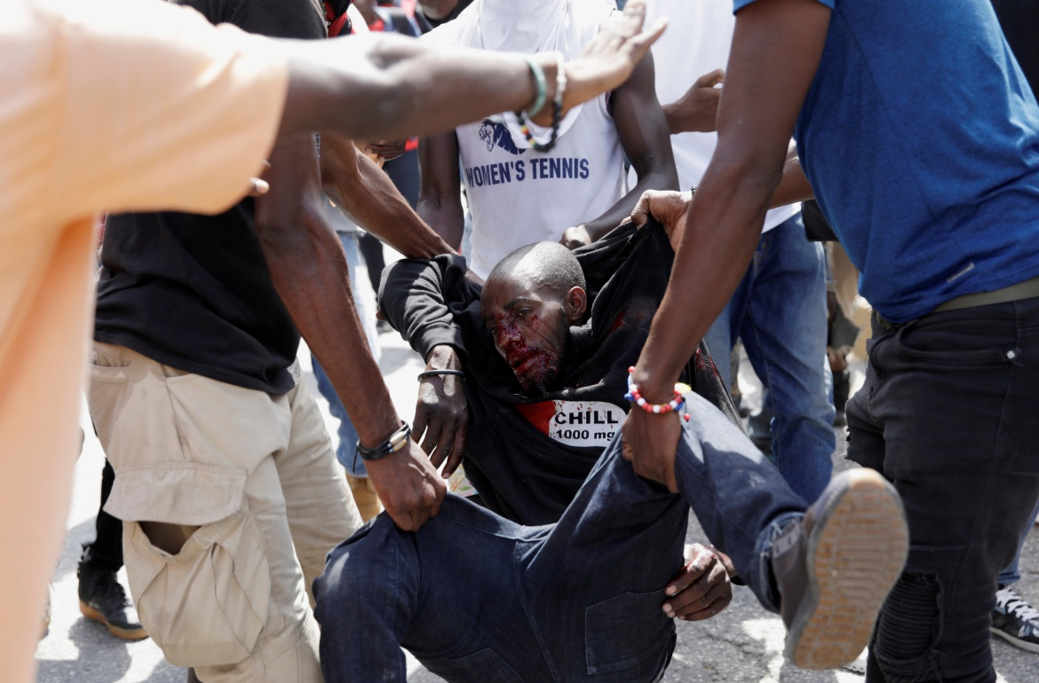 Demonstrators carry a man wounded during the protest in Port-au-Prince. [Andres Martinez Casares/Reuters]
