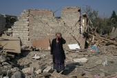 Regibe Guluyeva, 67, stands on the ruins of her home, which was hit by a rocket, in the city of Ganja, Azerbaijan October 18, 2020 [Umit Bektas/Reuters]