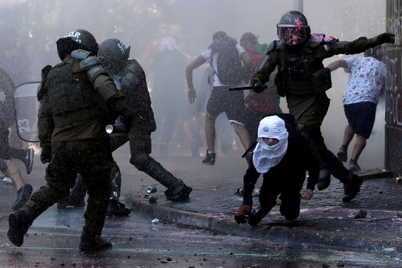 Riot police clash with demonstrators in Santiago. [Ivan Alvarado/Reuters]