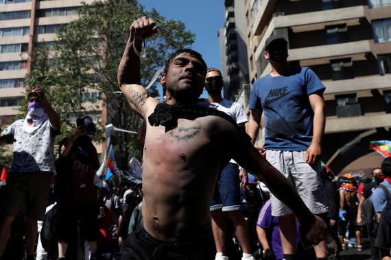 Tens of thousands took to the streets in Chile on Sunday, but the rallies descended into violence [Ivan Alvarado/Reuters]