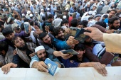 Afghan men in Jalalabad wait to collect tokens needed to apply for the Pakistan visa [Parwiz/Reuters] (Reuters)