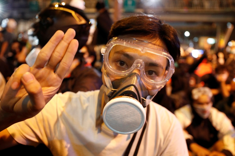 A pro-democracy protester makes a three-finger salute as he attends a march towards Government House during an anti-government protest in Bangkok, Thailand, on October 21, 2020 [Jorge Silva/ Reuters]