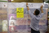 A retail worker covers French products on October 25, 2020 in protest against French cartoons of the Prophet Muhammad in Amman, Jordan. The cover reads in Arabic: 'In solidarity with the Prophet Muhammad, peace be upon him, all French products have been boycotted.' [Muhammad Hamed/Reuters]