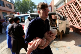 A man carries an injured child to a hospital after a truck bomb blast in Jalalabad on October 3, 2020 [File: Parwiz/Reuters]