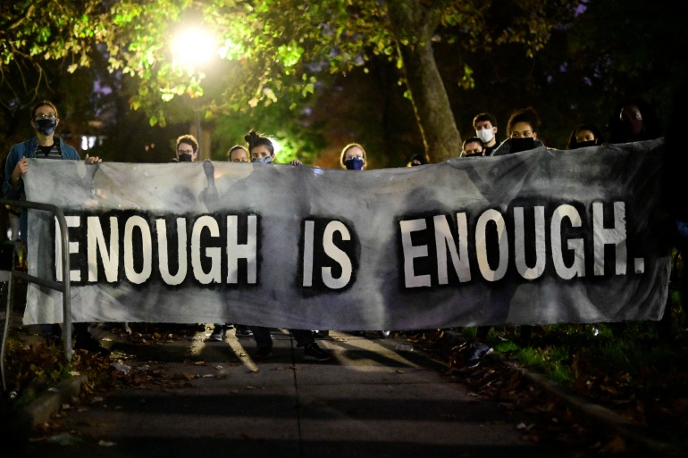 Protesters hold a banner reading 'enough is enough' during a rally after the death of Walter Wallace Jr, a Black man who was shot by police in Philadelphia, Pennsylvania [Bastiaan Slabbers/Reuters]