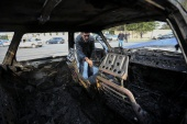 A man looks into a burnt car, which was hit by shelling during a military conflict over the breakaway region of Nagorno-Karabakh, in the town of Barda, Azerbaijan October 28, 2020. REUTERS/Aziz Karimov