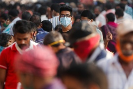 A man wearing a protective mask is seen at a crowded market in Mumbai [Francis Mascarenhas/Reuters]
