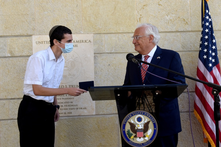 US Ambassador to Israel David Friedman presents Menachem Zivotofsky, a US citizen who was born in Jerusalem, a passport that lists Israel as his birthplace [Debbie Hill/Pool via Reuters]
