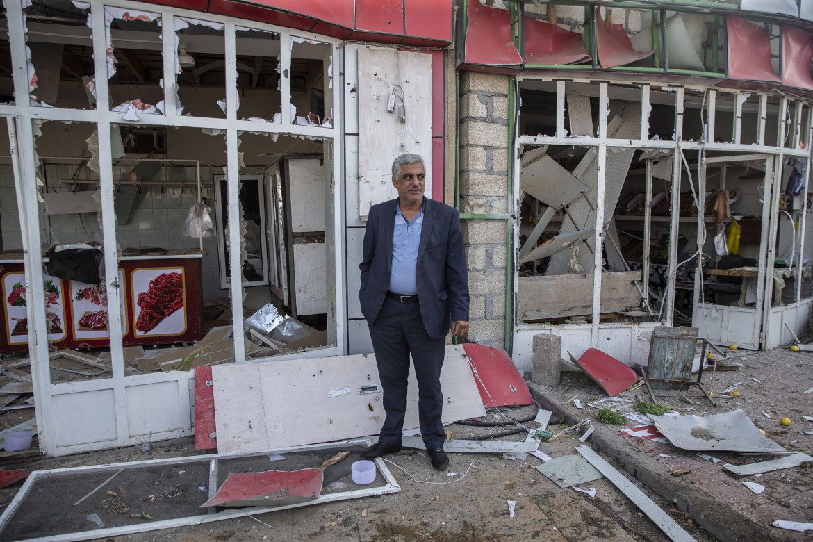 A man stands next to a damaged shop. The latest attacks came despite a US-brokered truce agreed less than a week ago, the third ceasefire attempt in a row to collapse just minutes after it took effect. [Arif Hüdaverdi Yaman/Anadolu]
