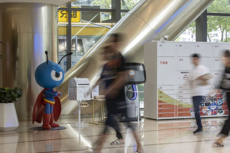 People walk past the Ant Group Co mascot displayed at the company's headquarters in Hangzhou, China [File: Bloomberg]