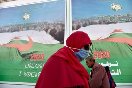 Algerians walk past campaign billboards ahead of the November referendum on constitutional reforms, on October 22, 2020, in Algiers [Ryad Kramdi/AFP]