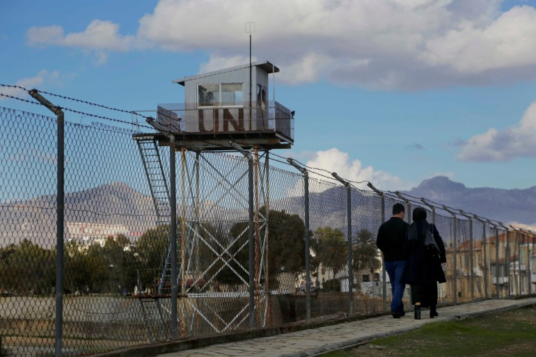 A couple walk past a UN guard post at the fence that divides the Greek and Turkish Cypriots areas in the eastern Mediterranean island of Cyprus on January 11, 2017 [File: AP/Petros Karadjias]
