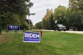 Signs for Democratic presidential candidate and former Vice President Joe Biden, and President Donald Trump mark properties in a middle-class neighbourhood of Oshkosh, the hub of swing-voting Winnebago County, Wisconsin [File: Thomas Beaumont/AP Photo]