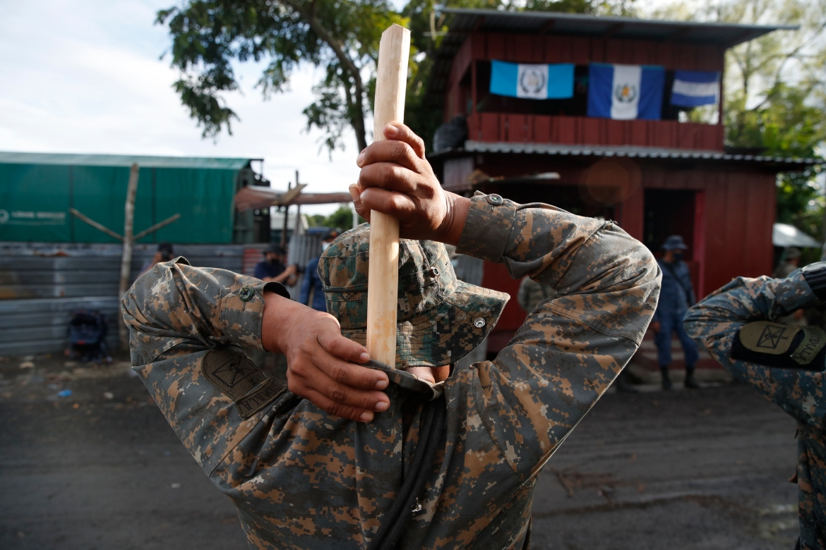 A soldier tucks a wooden stick into the back of his uniform as he stands guard in El Cinchado, Guatemala. [Moises Castillo/AP Photo]