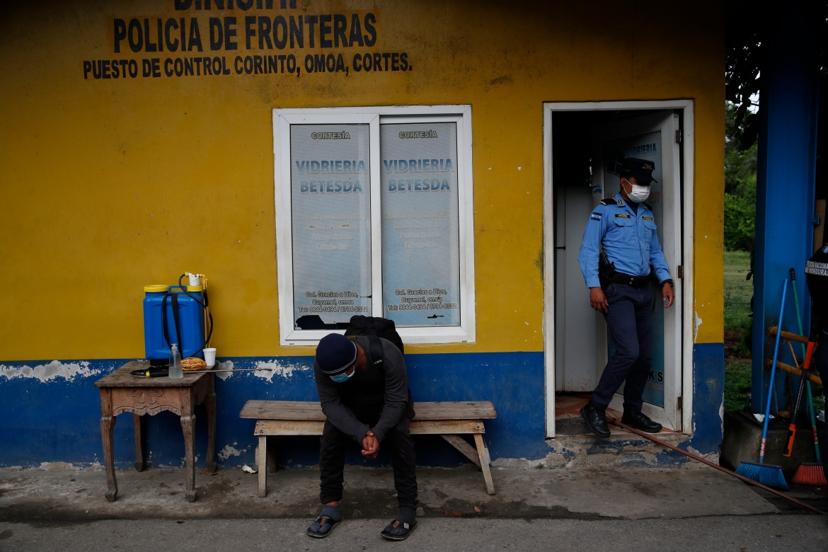 A Honduran migrant sits at a border police station in Corinto, Honduras, after he turned around and left behind the group of migrants he was traveling with in Guatemala. [Moises Castillo/AP Photo]