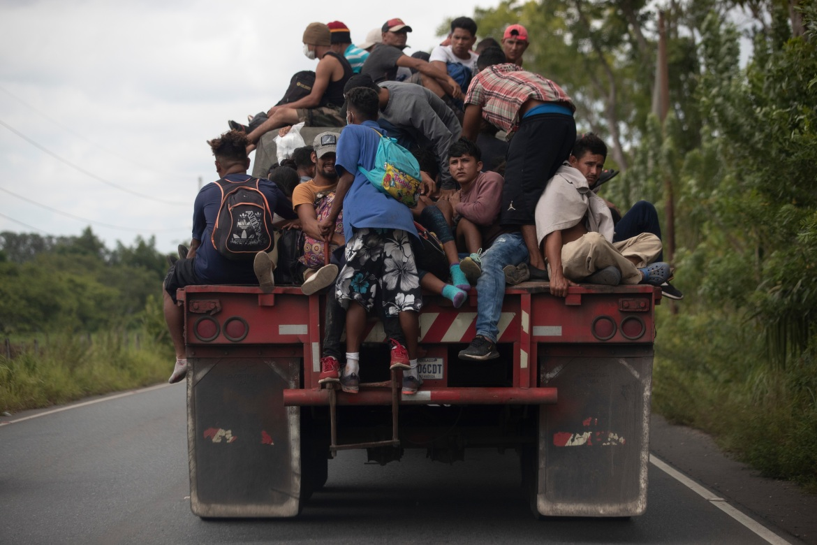 Migrants ride on the back of a freight truck in Rio Dulce, Guatemala. [Moises Castillo/AP Photo]