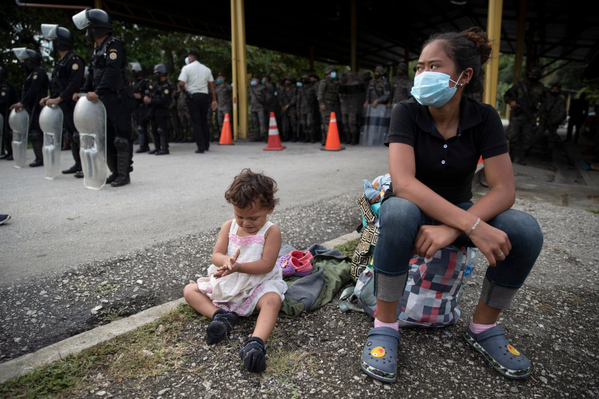 An Honduran migrant and her daughter sit at a roadblock set up by security forces in Poptun. Guatemala's tougher stance followed Mexico's hardened efforts that broke up caravans last October and in January at its southern border. [Moises Castillo/AP Photo]