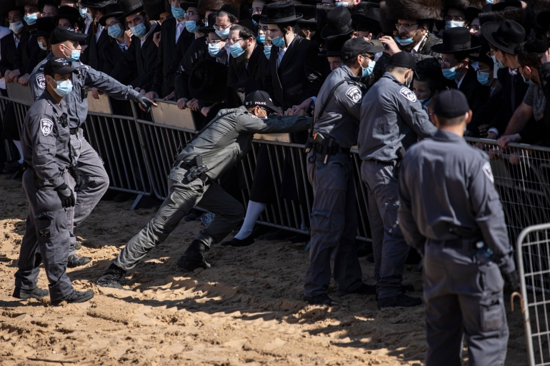 Israeli police try to control a crowd of mourners during the funeral of Rabbi Mordechai Leifer, the latest in a string of clashes between security forces and ultra-Orthodox Jews violating a national coronavirus lockdown order, in the port city of Ashdod, Israel on October 5, 2020 [AP/Tsafrir Abayov]