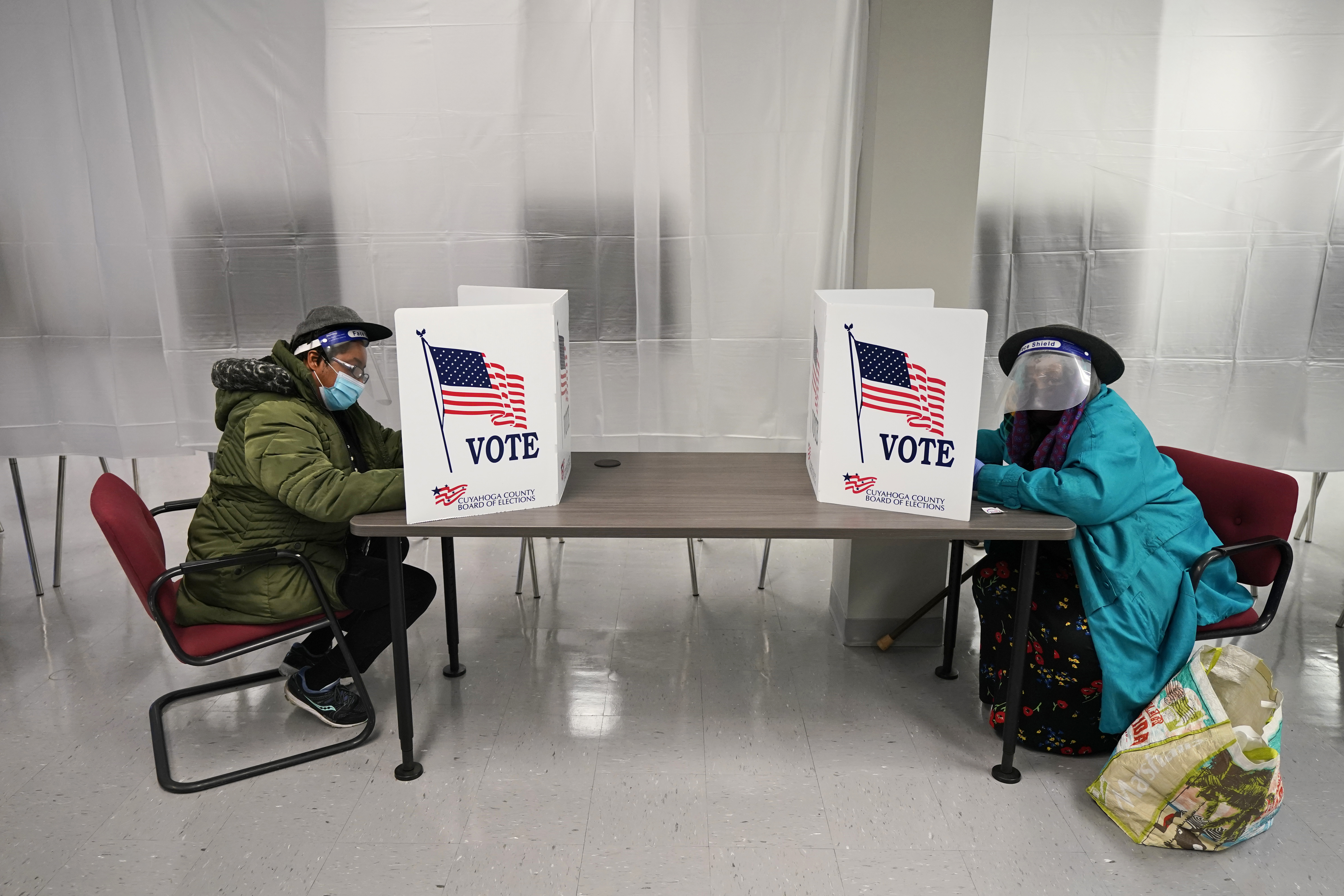 Two voters fill out ballots at the Cuyahoga County Board of Elections as early voting began in Ohio