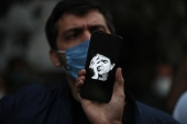 A fan displays an image of the famous singer Mohammad Reza Shajarian on his phone, outside the Jam Hospital where Shajarian died at the age of 80, in Tehran Iran, October 8, 2020 [AP Photo/Vahid Salemi]