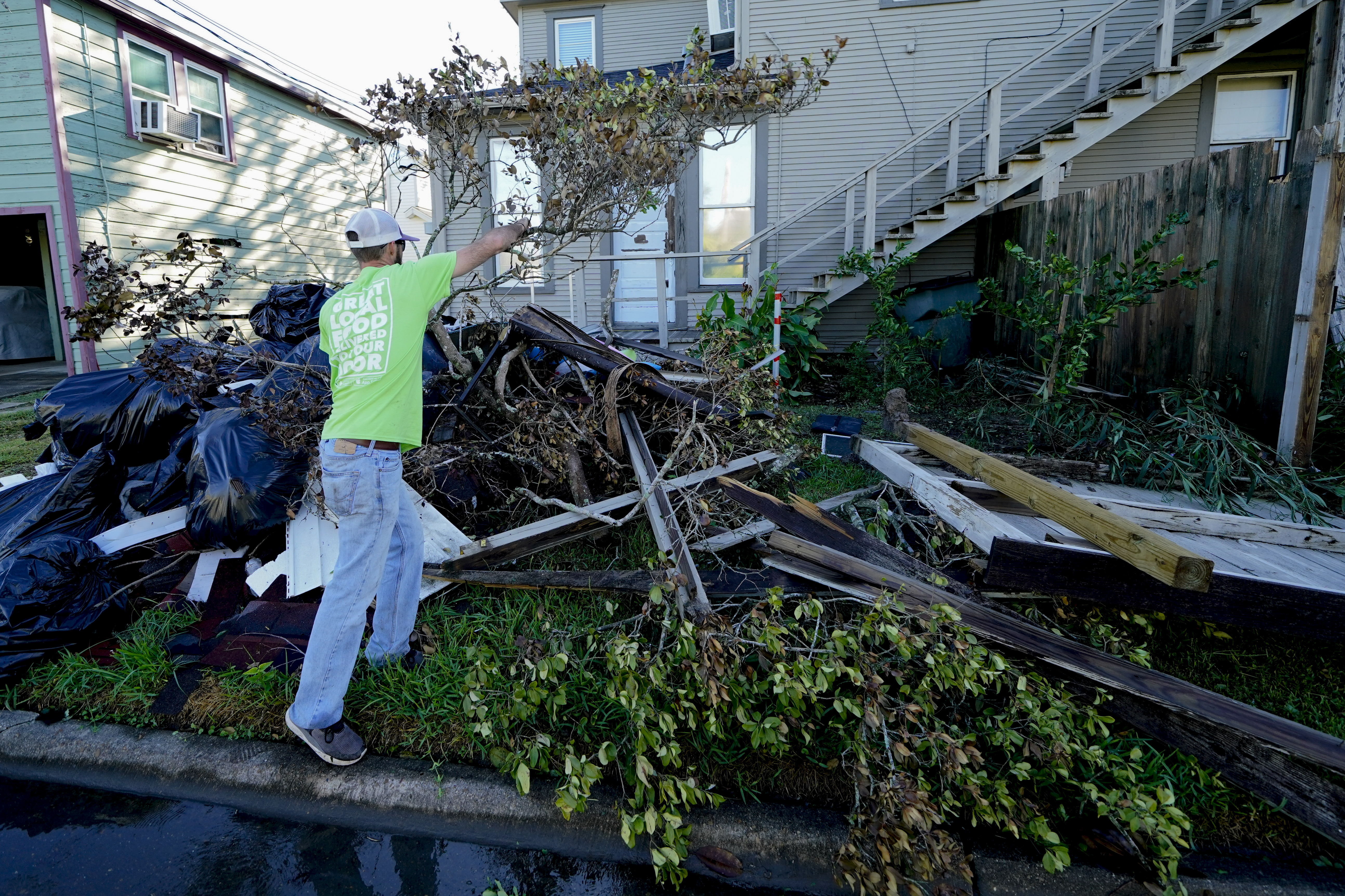Caleb Cormier moves debris after Hurricane Delta moved through Lake Charles