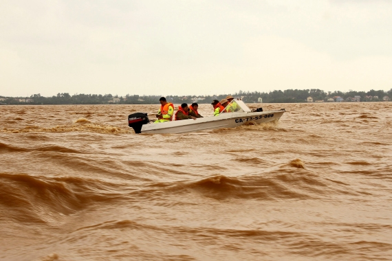 Rescue workers travel by boat on a swelling river to access a flooded area in Quang Binh province, Vietnam, on October 12, 2020 [Nguyen Van Ty/VNA via AP]