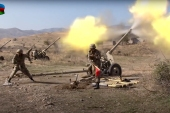 Azerbaijani soldiers fire an artillery piece during fighting on October 20, 2020 [Azerbaijan's Ministry of Defence/AP]