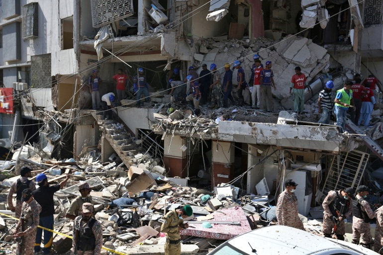 Pakistan's troops and rescue workers look for survivors amid the rubble of a damaged building following the explosion in Karachi. [Fareed Khan/AP Photo]
