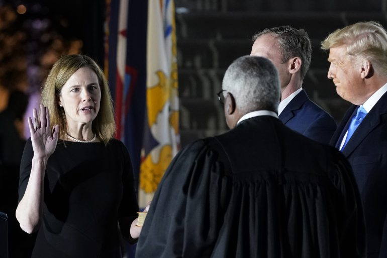 Judge Amy Coney Barrett takes the oath to join the US Supreme Court on the South Lawn of the White House in a controversial appointment just a week before the US presidential election [Patrick Semansky/AP Photo]