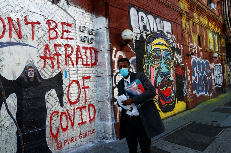 A man wearing a protective face mask as he walks by murals as the spread of COVID-19 continues in New York City [Shannon Stapleton/Reuters]