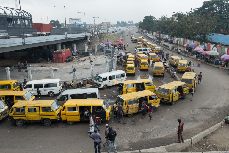 Buses queue by the side of the road to pick up passengers in Oshodi, one of the largest motor parks in Lagos [Anthony Obayomi/Al Jazeera]