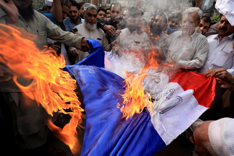 People set fire to France's flag in Peshawar, Pakistan, during a protest against the publication of Prophet Muhammad cartoons and comments by President Emmanuel Macron [Fayaz Aziz/Reuters]