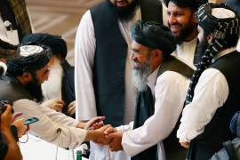 Taliban delegates shake hands during the intra-Afghan talks in Doha, Qatar on September 12, 2020 [Ibraheem al Omari/Reuters]