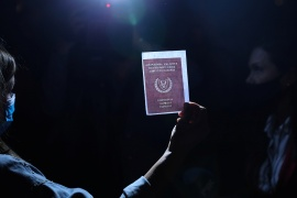 A person holds an image of a passport during a protest against corruption outside the Filoxenia Conference Center, currently hosting Cyprus parliament, in Nicosia, Cyprus October 14, 2020. [Yiannis Kourtoglou/Reuters]