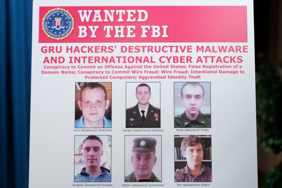 A poster showing six wanted Russian military intelligence officers is displayed before a news conference at the Department of Justice [Pool: Andrew Harnik/AP Photo]