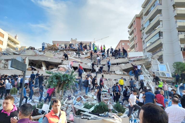 Residents and rescue workers search for survivors after a building collapsed in the coastal province of Izmir, Turkey, on Friday [Tuncay Dersinlioglu/Reuters]