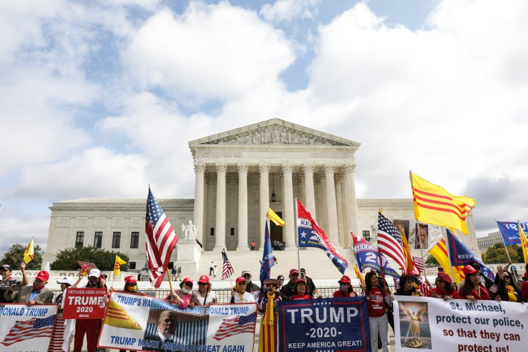 Vietnamese-American Trump supporters, who travelled across the United States in multiple caravans to Washington, DC, gather in front of the Supreme Court, waving US and South Vietnamese flags during the confirmation hearing of Justice Amy Coney Barrett on October 13, 2020 [Valerie Plesch/Al Jazeera]
