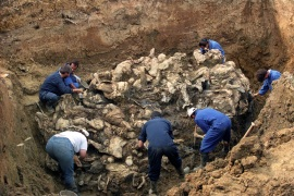 Investigators of the International War Crimes Tribunal work at a mass grave where they discovered the remains of more than 100 executed people outside the village of Pilica, Bosnia and Herzegovina, in September, 1996 [File: Odd Andersen/EPA-EFE]