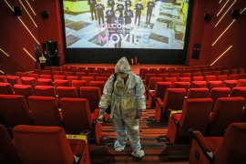 A worker disinfects seats at an INOX cinema hall in preparation for the reopening of cinema halls in Mumbai [Divyakant Solanki/EPA]