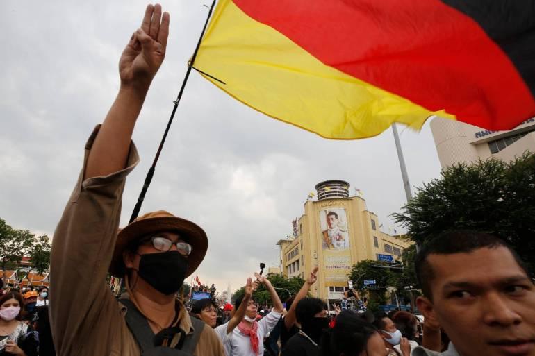 Seorang demonstran pro-demokrasi Thailand memberikan penghormatan protes tiga jari di samping potret Raja Maha Vajiralongkorn pada hari Rabu [Narong Sangnak / EPA]